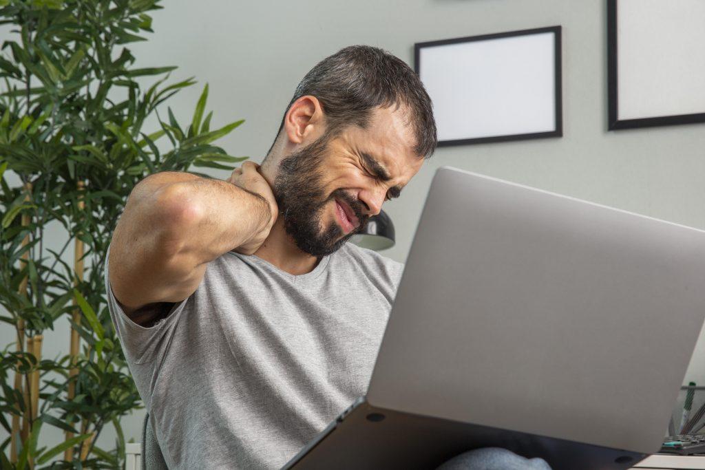 man experiencing neck pain while working from home on laptop 1024x683 - Ćwiczenia rozciągające odcinek szyjny mogą nasilać ból!